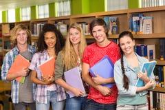 Studenci collegu trzyma książki w bibliotece Fotografia Stock