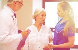 Studenci medycyny i starsza cierpliwa kobieta przy szpitalem Zdjęcia Stock