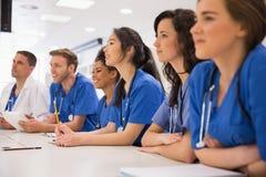 Studenci medycyny słucha siedzieć przy biurkiem Obraz Royalty Free