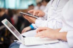 Studenci medycyny z ochraniaczem wewnątrz i laptopami Zdjęcia Stock