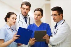 Studenci medycyny z schowka i pastylki komputerem osobistym przy szpitalem Fotografia Royalty Free