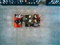 Studenci uniwersytetu siedzi w bibliotece zdjęcia stock