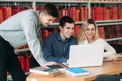 Studenci uniwersytetu siedzi wpólnie przy stołem z książkami i laptopem Szczęśliwi młodzi ludzie robi grupowej nauce w bibliotece Zdjęcia Royalty Free