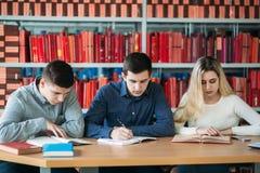 Studenci uniwersytetu siedzi wpólnie przy stołem z książkami i laptopem Szczęśliwi młodzi ludzie robi grupowej nauce w bibliotece Zdjęcia Stock