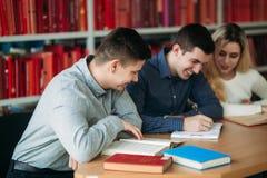 Studenci uniwersytetu siedzi wpólnie przy stołem z książkami i laptopem Szczęśliwi młodzi ludzie robi grupowej nauce w bibliotece Fotografia Stock