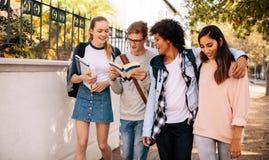 Studenci uniwersytetu z książkami w szkoła wyższa kampusie zdjęcie royalty free