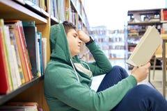 Studencka chłopiec lub młodego człowieka czytelnicza książka w bibliotece Zdjęcie Stock