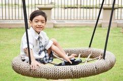 Studencka chłopiec sztuki huśtawka przy szkołą Zdjęcie Stock