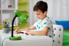 Studencka chłopiec w słuchawki czytelniczej książce w domu zdjęcia stock