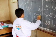 Studencka chłopiec w sala lekcyjnej writing na blackboard Zdjęcia Royalty Free