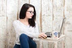 Studencka dziewczyna jest ubranym parę szkła studiuje na laptopu wh Obrazy Royalty Free