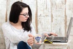 Studencka dziewczyna jest ubranym parę szkła studiuje na laptopu wh Fotografia Stock