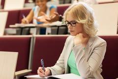 Studencka dziewczyna pisze notatnik w odczytowej sala Obrazy Stock
