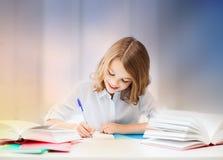 Studencka dziewczyna pisze w notatniku z książkami Fotografia Royalty Free