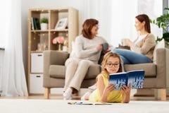 Studencka dziewczyna uczy się w domu z podręcznikiem obraz stock