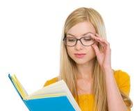 Studencka dziewczyna w szkło czytelniczej książce fotografia royalty free
