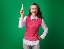 Studencka kobieta pokazuje kawałek kreda na zielonym tle fotografia stock