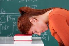 Studencka oparta głowa na książce w sala lekcyjnej Obrazy Royalty Free