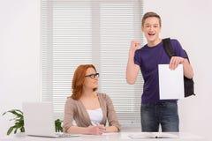 Studencka pozycja w klasowy szczęśliwym z papierkową robotą Obrazy Stock