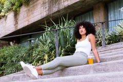 Studencka turystyczna dziewczyna z afro fryzury obsiadaniem w staircas zdjęcie royalty free