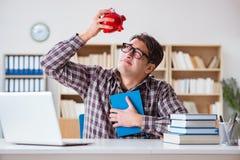 Studencki łamania piggybank płacić dla opłata za lekcje obraz stock