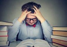 Studencki młody człowiek z desperackimi wyrażeniowymi patrzeje książkami obraz stock