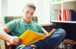 Studencki obsiadanie na krześle i czytelniczej książce Zdjęcia Stock