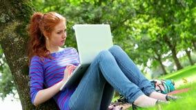 Studencki obsiadanie przeciw drzewu używać jej laptop zbiory