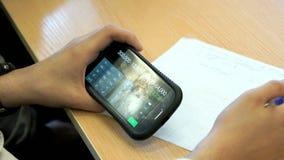 Studencki obsiadanie przy biurkiem trzyma telefon komórkowego zbiory