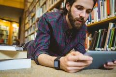 Studencki studiowanie na podłoga jest ubranym mądrze zegarek w bibliotece obraz royalty free