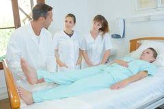 Studenckie pielęgniarki ogląda doktorskiego dźwignięcia cierpliwego ` s iść na piechotę zdjęcia stock