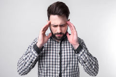 Studenh holding his head with his hands. Businessman gets stress. Bearded man on a white background royalty free stock photography