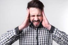 Studenh que lleva a cabo su cabeza con sus manos El hombre de negocios consigue la tensión Hombre barbudo en un fondo blanco Imagen de archivo libre de regalías