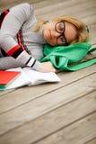 Studenka di sonno con il taccuino aperto sul pavimento di legno Fotografia Stock