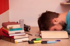 Student überschritt heraus mitten in einem großen Buch beim Studieren Lizenzfreie Stockfotos