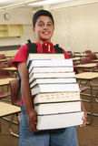 Student. A boy student carrying a large stack of books in the classroom Royalty Free Stock Photo