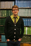 Student. Male student with glasses standing in front of books in library smiling into camera Royalty Free Stock Photos