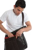 Student. Male student placing a book into a brown leather satchel.  White background Stock Image