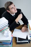 Student. Young puzzled man sitting at the table with blank paper Stock Images