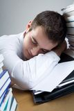 Student. Young man sitting at the table with blank paper, sleeping Royalty Free Stock Images