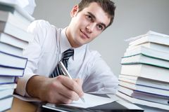 Student. Young puzzled man sitting at the table with blank paper Stock Photos