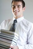 Student. Young man standing with books, smiling Stock Photography