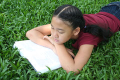 Student 2. Girl reading book in the park Royalty Free Stock Image