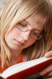 Student. Portrait of a pretty blond caucasian teenager reading a book Stock Image