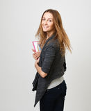 Student. Young gay girl turns to notebooks in their hands. IIsolated gray background Stock Photo