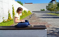 Student. Laughing student girl sitting on the bench with laptop Royalty Free Stock Photo