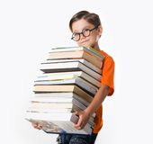 Student. Portrait of diligent student in glasses with heap of books in hands Royalty Free Stock Photography