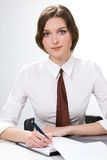Student. Portrait of pretty student wearing tie sitting at table with pen over notebook and looking at camera Stock Photography