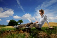 Student. Young man sitting in countryside with laptop Royalty Free Stock Images
