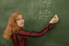 Student. Young woman are standing with chalk in hand close to chalkboard with formulas Stock Photography